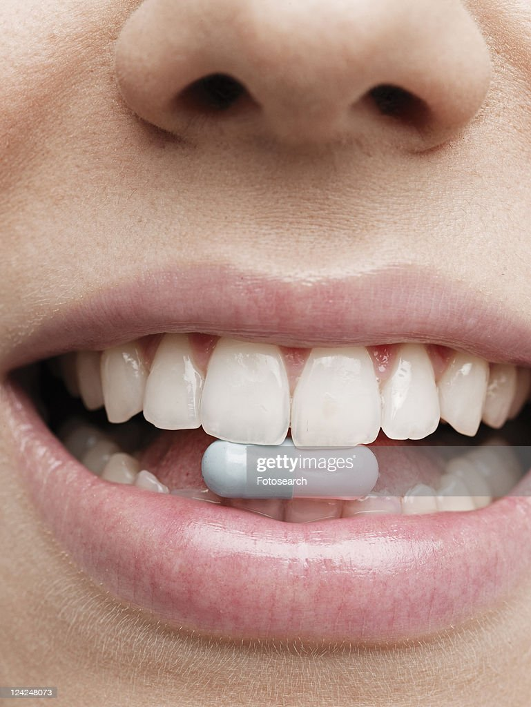 Woman holding vitamin pill in teeth : Stock Photo