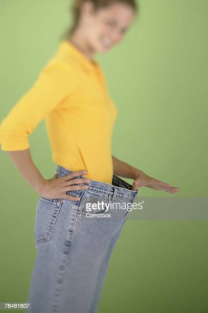 woman holding waistband of large pants - waistband stock pictures, royalty-free photos & images
