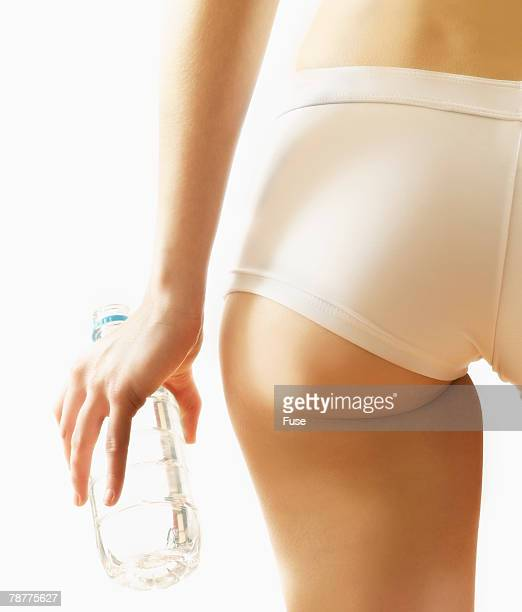 woman holding water bottle - fesses culotte photos et images de collection