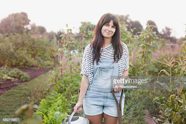 Woman holding watering can and fork on allotment