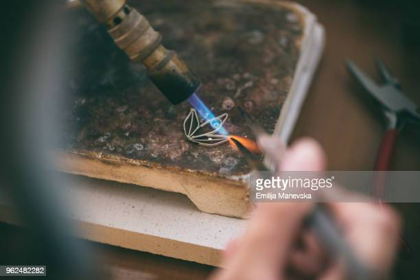 woman holding welding torch and melting silver in her workshop - jewellery products stock photos and pictures