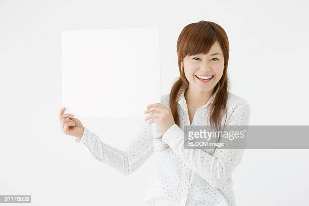 Woman holding white board, studio shot