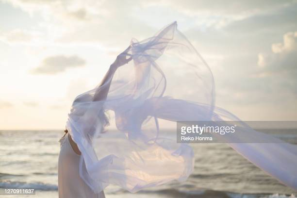 woman holding white sheer fabric on the beach - sheer fabric stock pictures, royalty-free photos & images