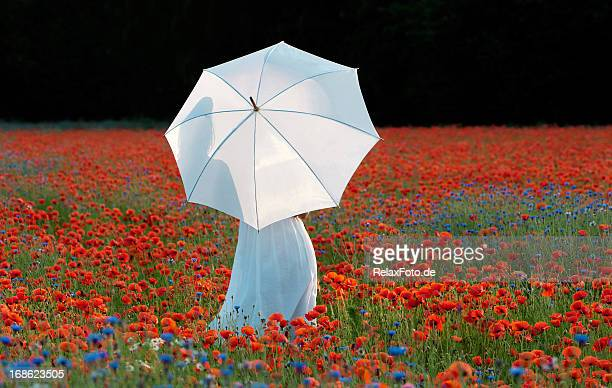 woman holding white umbrella standing in large poppy field - impressionism stock photos and pictures