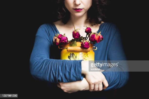 woman holding wilted roses - menopause stock pictures, royalty-free photos & images