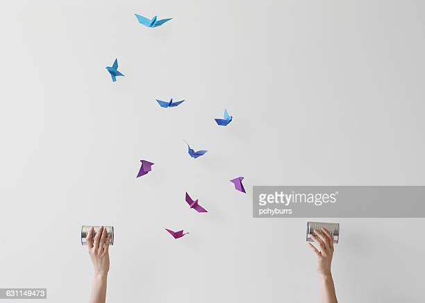 Woman holding wireless tin can phones with conceptual birds flying mid air