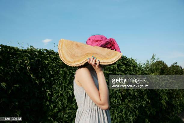 Woman Holding Wood While Standing Against Hedge