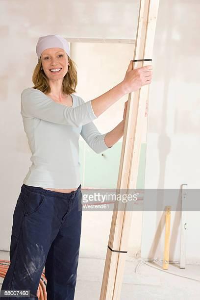 Woman holding wooden planks, smiling, portrait