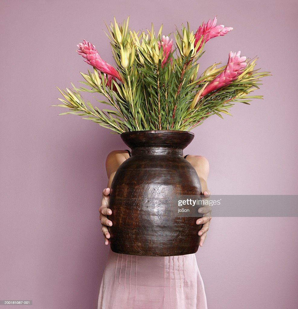 Woman Holding Wooden Vase With Pink Ginger Flower Stock Photo