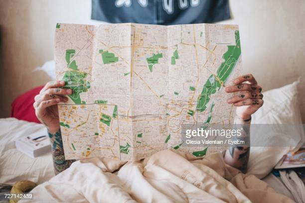 Woman Holding World Map While Lying On Bed At Home