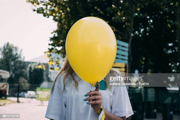 woman holding yellow balloon in front of face against trees - yellow photos et images de collection