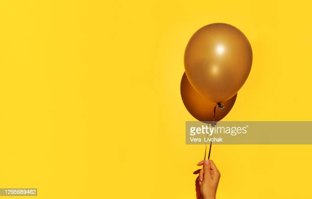 woman holding yellow balloon on color background - anniversary stock pictures, royalty-free photos & images