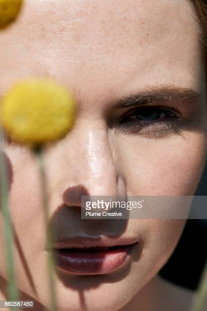 Woman holding yellow flowers in front of face