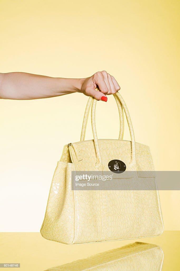 Woman holding yellow handbag : Stock Photo