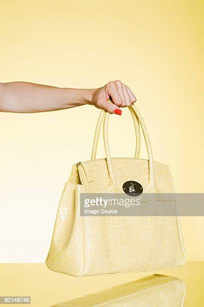 Woman holding yellow handbag