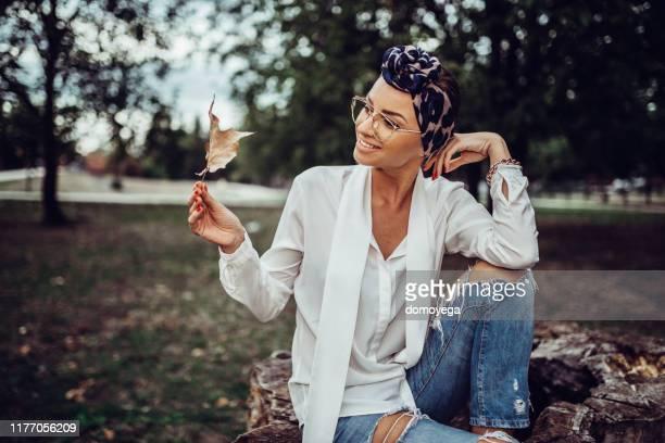 晴れた秋の日に黄色い葉を持つ女性 - ヘッドスカーフ ストックフォトと画像