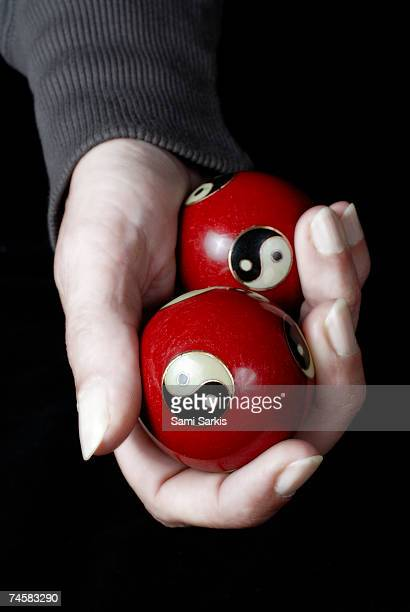 Woman holding Yin Yang balls in hand, close up of hand
