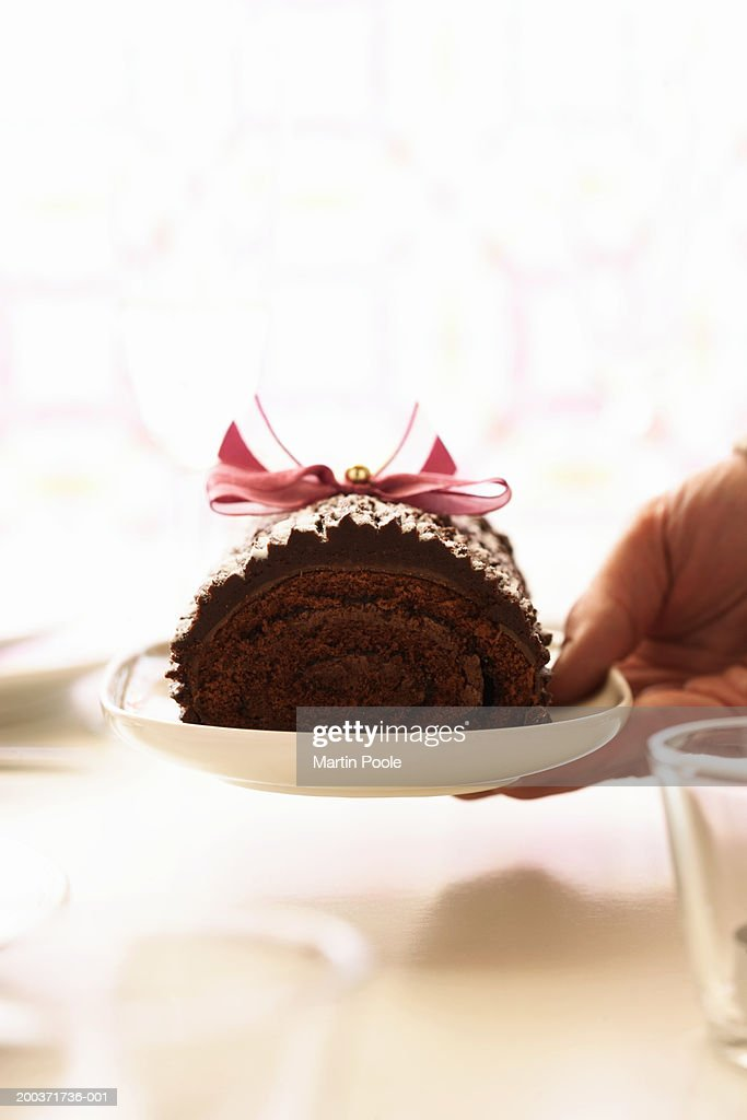 Woman holding yule log on plate, close up : Stock Photo
