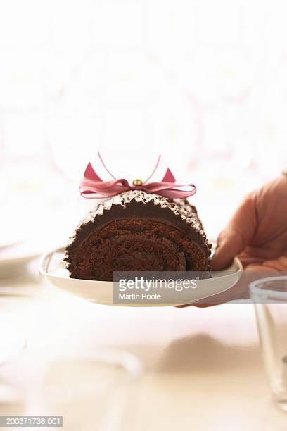 Woman holding yule log on plate, close up