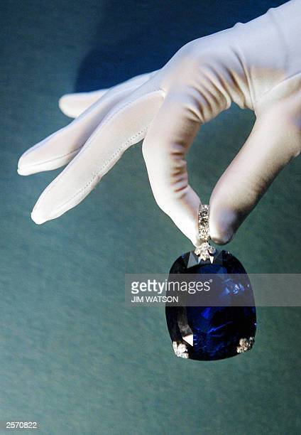 Woman holds a 478 carat sapphire which was previously owned by Queen Marie of Romania 08 October 2003 at Christie's in London. The piece highlights...
