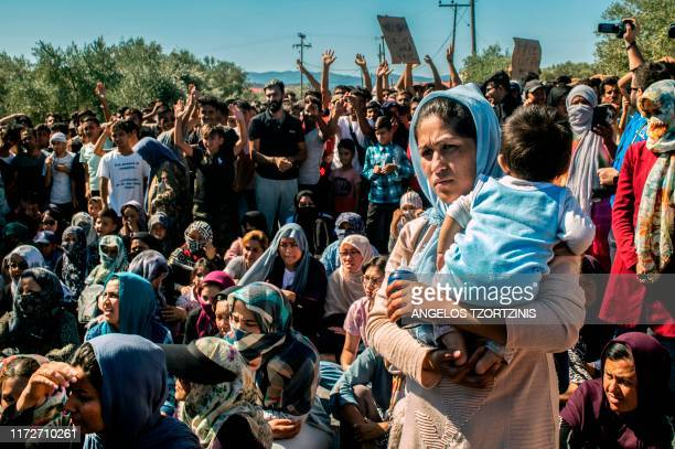 Woman holds a baby as refugees and migrants take part in a demonstration against their living conditions at the Moria camp on the island of Lesbos,...