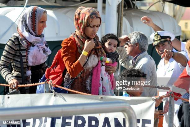 A woman holds a baby as she disembarks from rescue ship Aquarius run by NGO 'SOS Mediterranée' after a rescue operation at sea on October 13 2017 in...