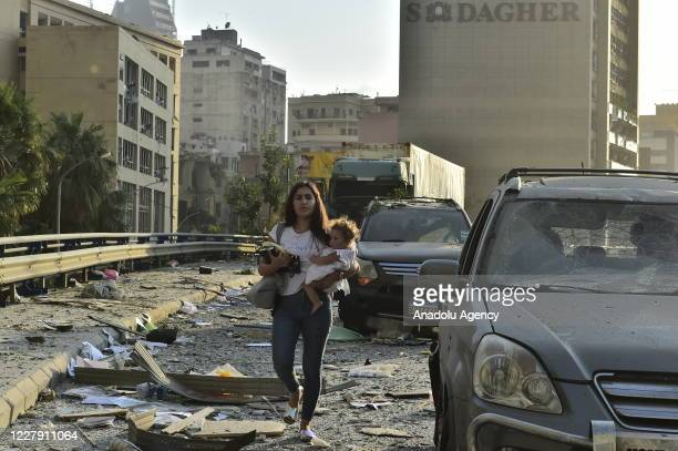 Woman holds a baby as she walks at a damaged site after a fire at a warehouse with explosives at the Port of Beirut led to massive blasts in Beirut,...