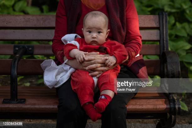 Woman holds a baby at a local park on May 12, 2021 in Beijing, China. According to data released by the government from a national census, China's...
