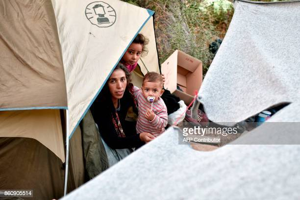 A woman holds a baby at a makeshift tent camp near the overcrowded hotspot on the Greek eastern Aegean islands of Samos on October 13 2017 More than...