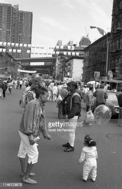 A woman holds a baby bottle as she stands by a young girl with a helium balloon on 9th Avenue in Hell's Kitchen during the International Food...