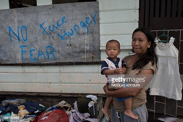 """Woman holds a baby in front of a home with a """"no fear face hunger"""" written on the wall in Tanauan, on the outskirts of Tacloban on November 16, 2013...."""