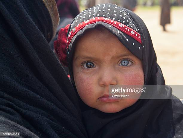 A woman holds a baby with Heterochromia of the eye as she listens to Muzaffar Hussain Beigh Kashmir's former deputy chief minister and a senior...