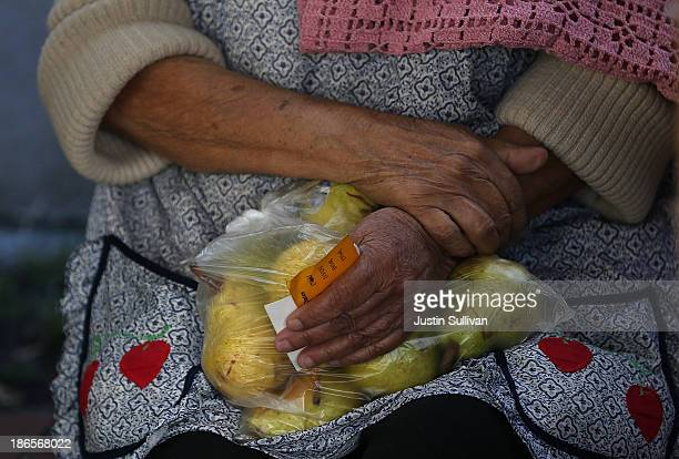 A woman holds a bag of pears as she waits in line to receive free food at the Richmond Emergency Food Bank on November 1 2013 in Richmond California...