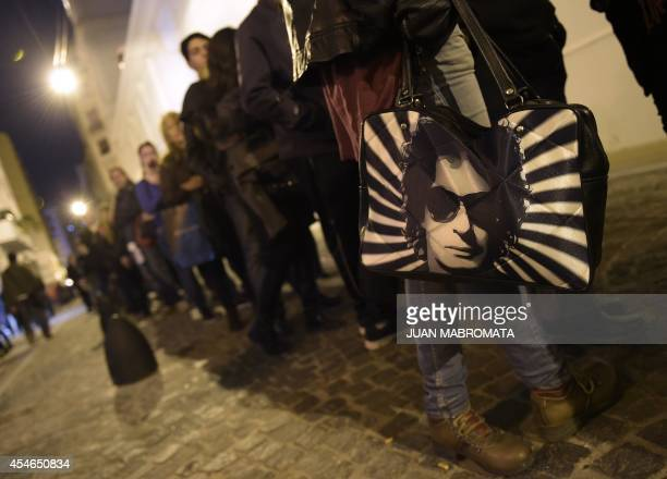 A woman holds a bag with a portrait of late Argentine musician Gustavo Cerati while lining up during his funeral near the legislative building in...