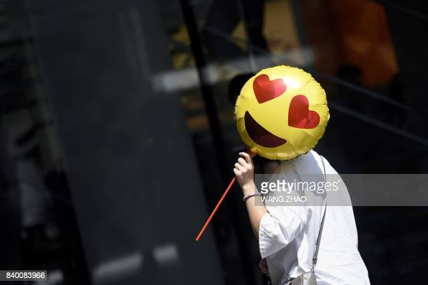 A woman holds a balloon as she walks past a store on Chinese Valentine's Day in Beijing on August 28 2017 Qixi Festival or Chinese Valentine's Day...