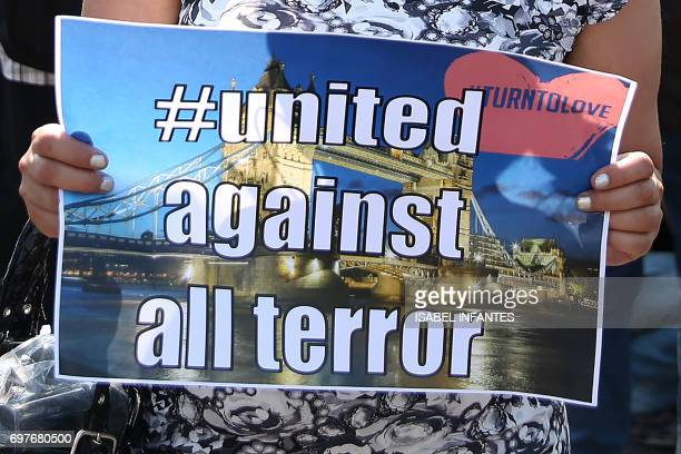 A woman holds a banner as she stands art a Police cordon close to the scene of a van attack in Finsbury Park north London on June 19 2017 Ten people...