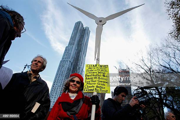 A woman holds a banner as she takes part in a global climate march near City Hall on November 29 2015 in New York City The protest is part of an...