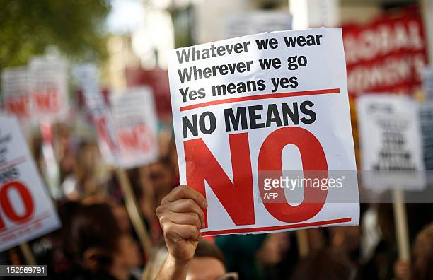 A woman holds a banner as she takes part in a 'slut walk' in London on September 22 2012 to protest against the police and courts' denial of justice...