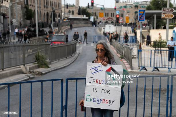 A woman holds a banner at Damascus gate in Jerusalem on May 13 as Israeli nationalist settlers celebrate the Jerusalem Day in the Old City For...
