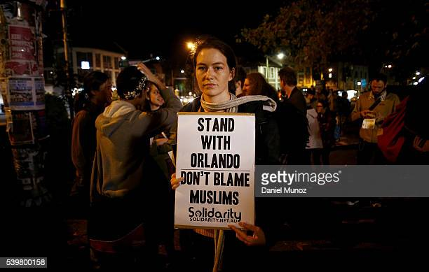 A woman holds a banner during a candlelight vigil for the victims of the Pulse Nightclub shooting in Orlando Florida at Newtown Neighbourhood Centre...