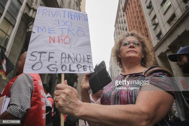 A woman holds a banner during a demonstration against employee layoffs and the expansion of the privatization of subway lines in front of the subway...