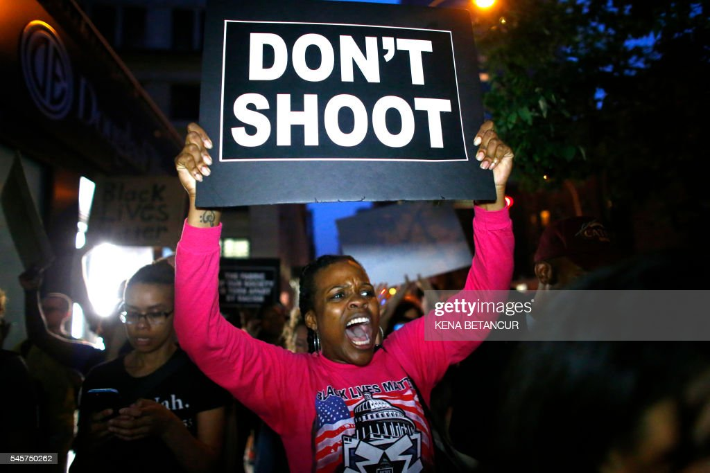 TOPSHOT - A woman holds a banner during a protest in support of the Black lives matter movement in New York on July 09, 2016. The gunman behind a sniper-style attack in Dallas was an Army veteran and loner driven to exact revenge on white officers after the recent deaths of two black men at the hands of police, authorities have said. Micah Johnson, 25, had no criminal history, Dallas police said in a statement. /