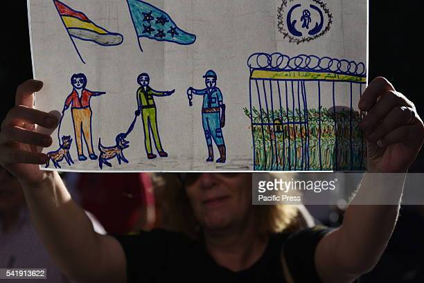 A woman holds a banner painted by a child refugee in Idomeni during a protest in Madrid in support of refugees and migrants An estimated 100 people...