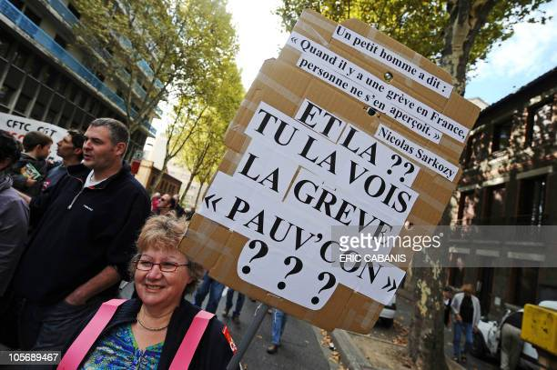 A woman holds a banner reading 'Can you see the strike now 'asshole'' as she walks in the street of the southern city of Toulouse on October 2 during...