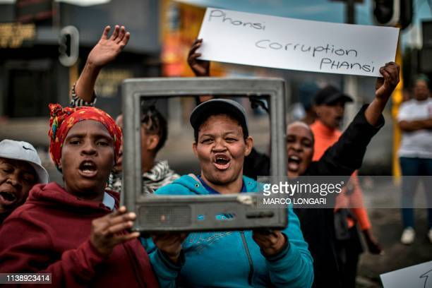 TOPSHOT A woman holds a banner reading down with corruption as they shout slogans and gesture in Johannesburg on April 23 2019 during a protest...