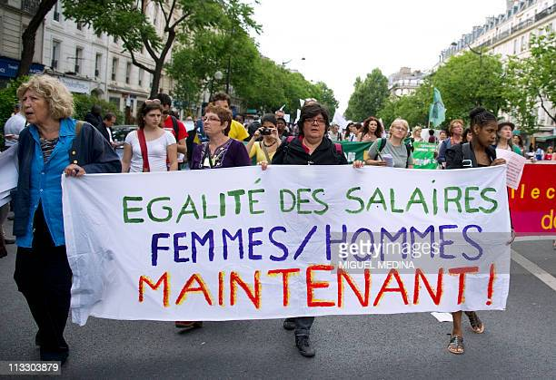 """Woman holds a banner reading """"Equal pay women/men now"""" as people take part in a march as part of the annual May Day workers' events on May 1, 2011 in..."""