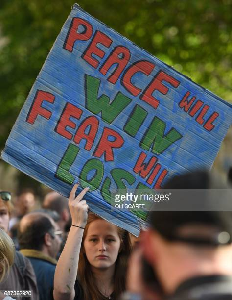 A woman holds a banner reading 'Peace will Win Fear will Lose' during a vigil in Albert Square in Manchester northwest England on May 23 in...