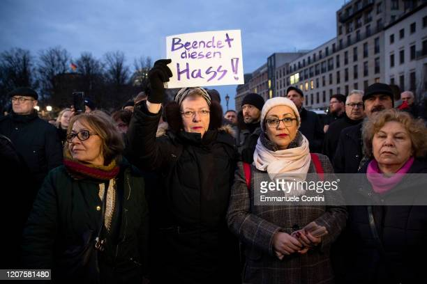 A woman holds a banner reading 'Stop this hate' during a vigil at the Brandenburg Gate to commemorate the victims of the Hanau shootings on February...