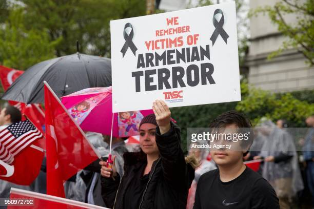 A woman holds a banner reading We Remember The Victims Of Armenian Terror during a demonstration in front of the Turkish Embassy in the US capital to...