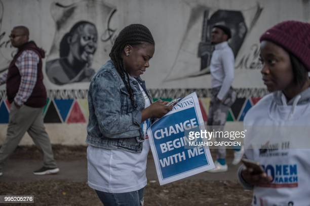 A woman holds a banner that reads 'Change begins with me' as she takes part in the 100 Men March as thousands of other demonstrators aim to march to...
